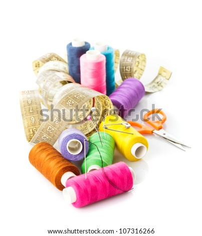 Sewing items: multicoloured threads, pins, meter and scissors on white - stock photo