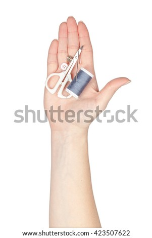 sewing kit in a hand isolated on white background
