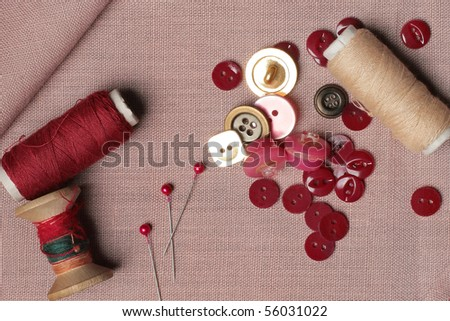 Sewing kit. Red and bright gold buttons and three bobbins on the pink background - stock photo