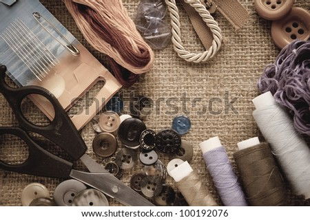 Sewing kit. Scissors, bobbins with thread and needles on the old fabric. - stock photo