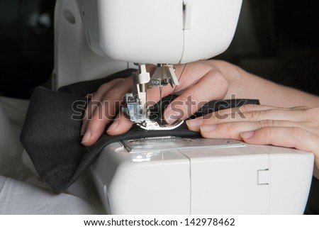 sewing machine and black fabric - stock photo