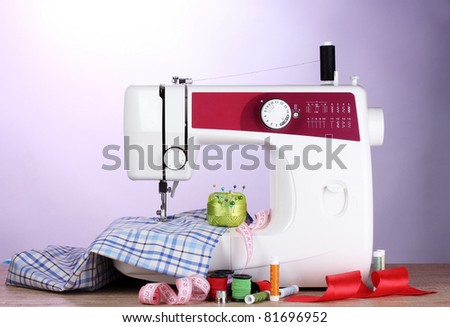 sewing machine and fabric on purple background - stock photo