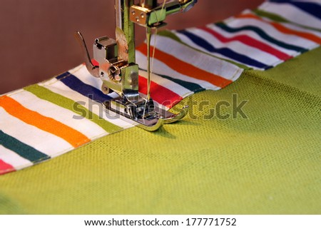 Sewing machine and item of clothing material  - stock photo