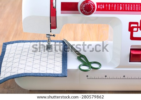 Sewing machine and sewing accessories on wooden table - stock photo