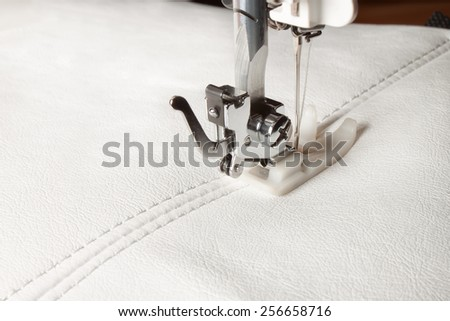 sewing machine and white leather with a seam close-up - stock photo