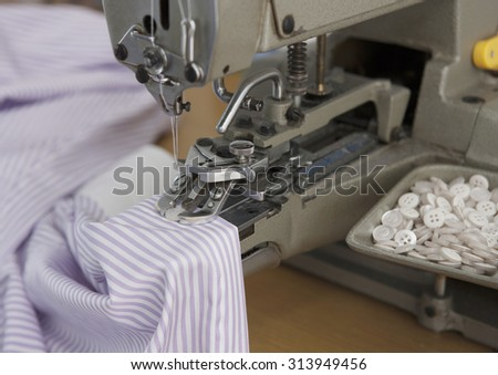 sewing machine close up with in action with a tshirt
