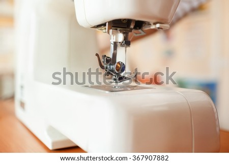 Sewing machine needle working part, detail of sewing machine and sewing accessories, modern white sewing machine, ready to sew, perspective wide angle. - stock photo