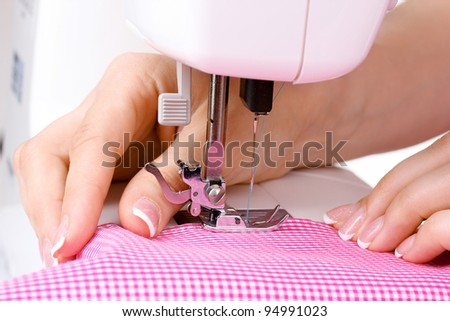 sewing machine, red fabric and women's hands - stock photo
