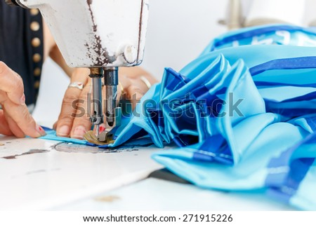Sewing machine with hands of a tailor - stock photo