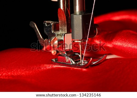 Sewing machine with red cloth closeup - stock photo