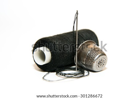 Sewing Needle, thimble and thread spool on a white background - stock photo