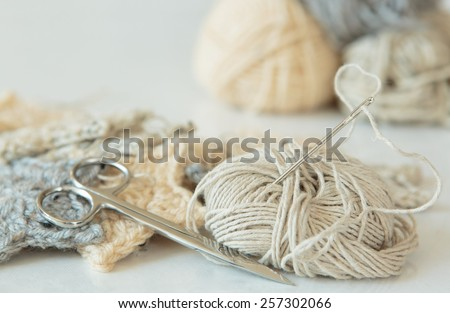 Sewing needle threaded with hemp, yarn, crochet, and scissors in neutral colors - stock photo