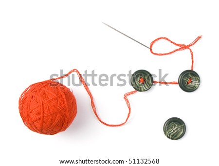 Sewing needle with red ball of threads and buttons - stock photo