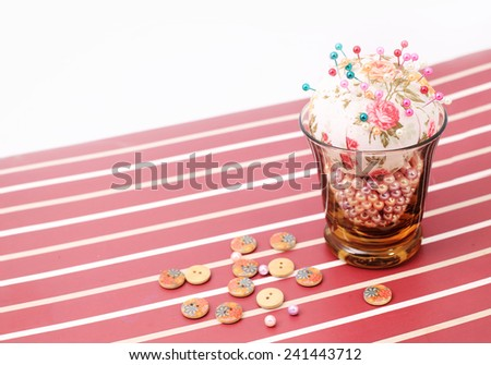 Sewing pins and pin cushion in the glass. - stock photo