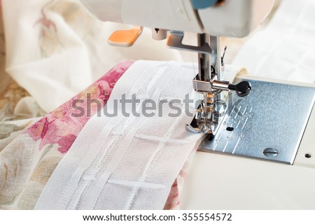 sewing process by a curtain tape on the sewing machine - stock photo