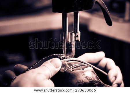 Sewing process of the leather belt. Man's hands behind sewing. Leather workshop. Black and white photography. Cream toned. - stock photo