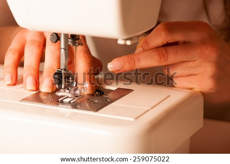 Sewing Process - Women taylor's  hands behind her sewing machine - stock photo