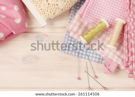 Sewing set: fabrics and threads on wooden table - stock photo