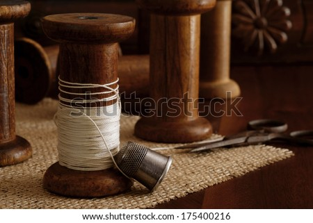 Sewing still life with antique thimble, scissors and wooden spools (from old textile mill - circa 1900). Antique sewing machine drawer in background. Macro with shallow dof. - stock photo