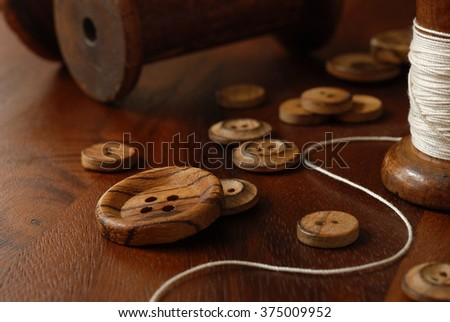 Sewing still-life with vintage wooden buttons and antique thread spools (from old textile mill - circa 1900) on dark, rustic wood.  Macro with soft, natural lighting and shallow dof.  - stock photo