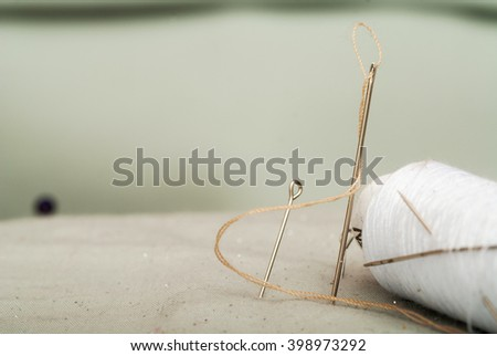 Sewing textile or cloth. Work table of a tailor. Detail of a needle with thread in the workroom reel of thread, and natural fabric.  - stock photo