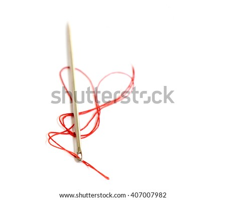 Sewing thread and needle on a white background closeup