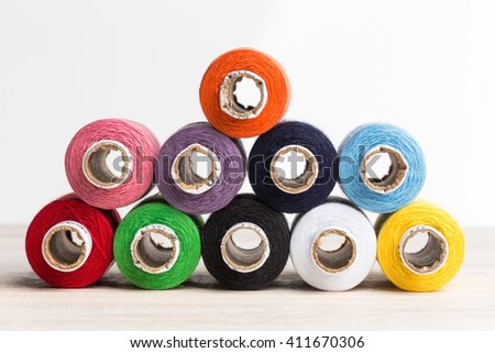 Sewing threads of different colors stacked side by side on a wooden surface. - stock photo