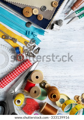 Sewing tools and accessories on white painted wooden background - stock photo