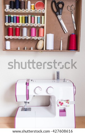Sewing tools and sewing kit in a wooden box with a sewing machine