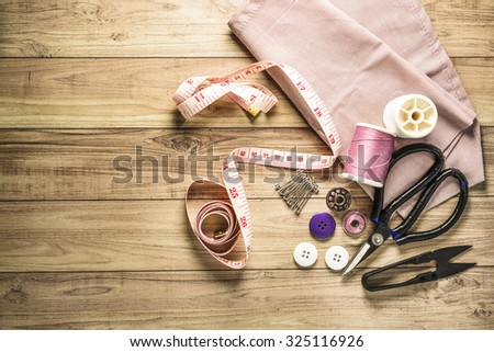 Sewing tools and sewing kit on wooden textured background - stock photo