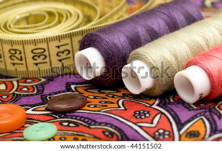 sewing tools on colorful fabric background