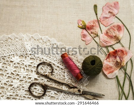Sewing tools on linen cloth with lace and dry poppies looks like embroidery - stock photo