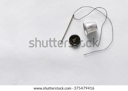 Sewing tools on white fabric background.Needle, thread, thimble and button. Horizontal composition. Top view - stock photo