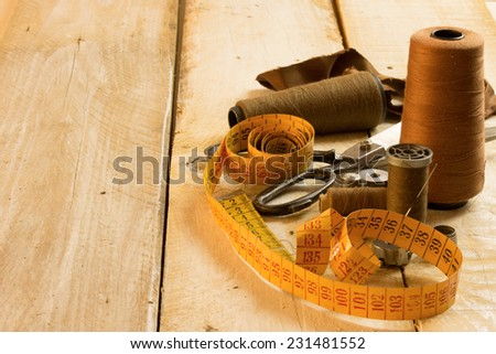sewing tools: tape measure,bobbins on a wooden surface - stock photo
