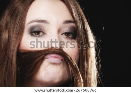 Sex equality and feminism concept - woman teen girl with hair moustaches making silly face on black - stock photo