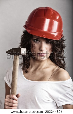 Sex equality and feminism. Sexy girl in safety helmet holding hammer tool. Attractive woman working as construction worker. - stock photo