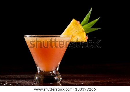 sex on the beach cocktail served on a bar garnished with a pineapple slice