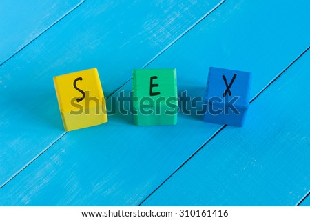 Sex - word on children's colourful cubes or blocks. Colourful wooden background.