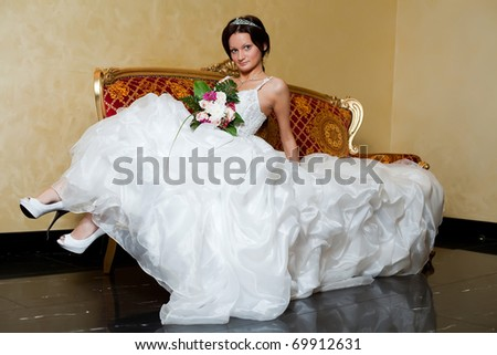 Sexi bride relaxing on love seat. - stock photo