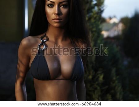 Sexual beauty dressed in bikini poses near building - stock photo
