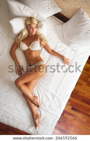 Sexual blonde woman lying on white bed - stock photo