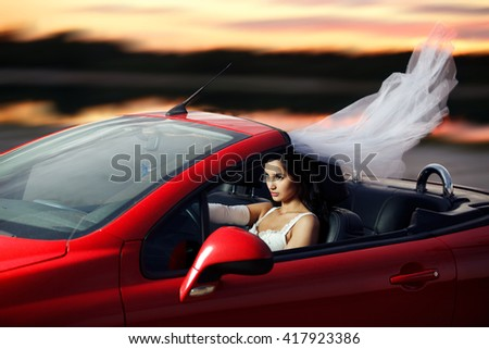 Sexual bride riding in a red sports car