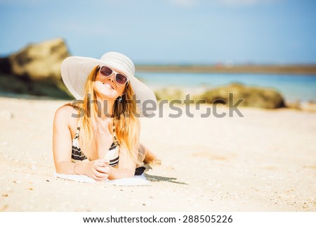 Sexual brunette girl take sunbath on the beach, happy female in  swimwear, sunglasses and white hat enjoying summer holidays leying on white sand. Holidays, vacation, lifestyle concept. Copyspace - stock photo