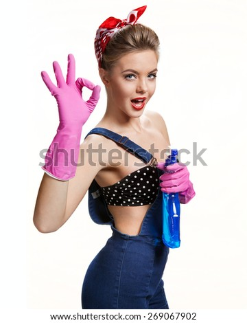 Sexual cleaning babe wearing pink rubber protective gloves holding spray Showing Us It's Okay / young beautiful American pin-up girl isolated on white background. Cleaning service concept - stock photo