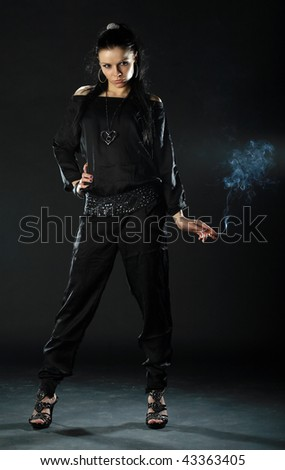 Sexual girl poses with a sigarette on a black background