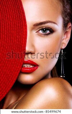 sexual girl with the sexual magnificent red lips covers half of face by the red cap - stock photo