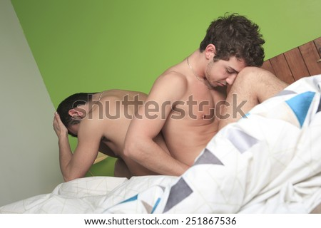 Sexual life - gay couple on the bed - stock photo