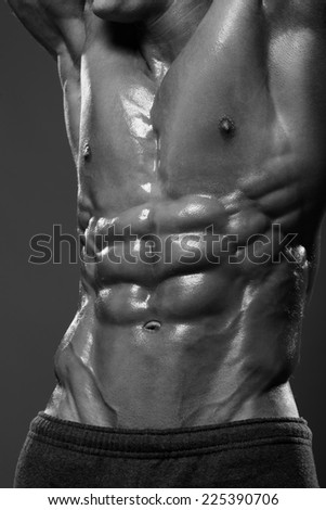Sexual portrait of very muscular man's model without shirt on a gray background in studio