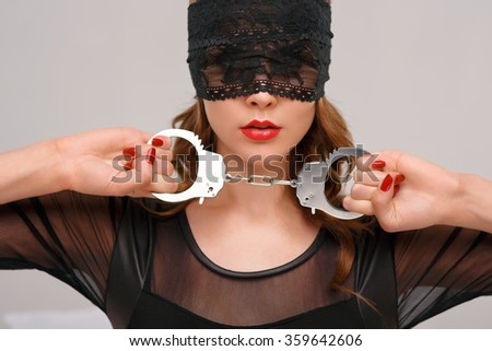 Sexual woman holding handcuffs.  - stock photo