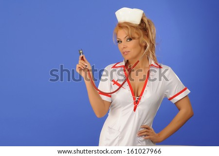 Sexual woman in nurse suit with stethoscope blue background  - stock photo